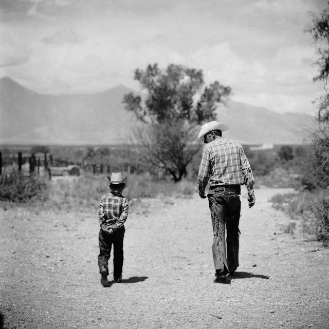 united states   july 01  rancher james a shugart walking a dusty road with son james jr  photo by allan grantthe life picture collection via getty images