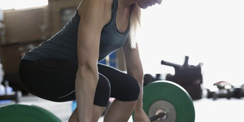 Strong woman weightlifting, doing barbell deadlift at gym