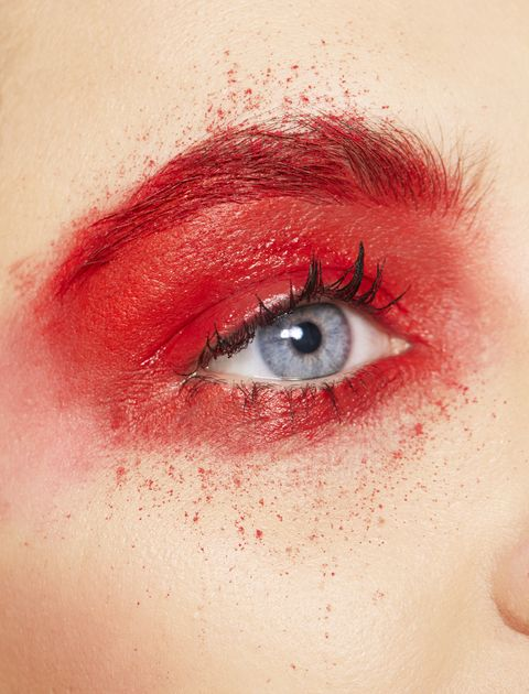 Close up of young womans eye with red eye shadow