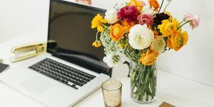 Flowers in jar near laptop in office