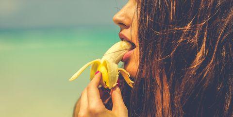 Close-Up Of Woman Eating Banana At Beach