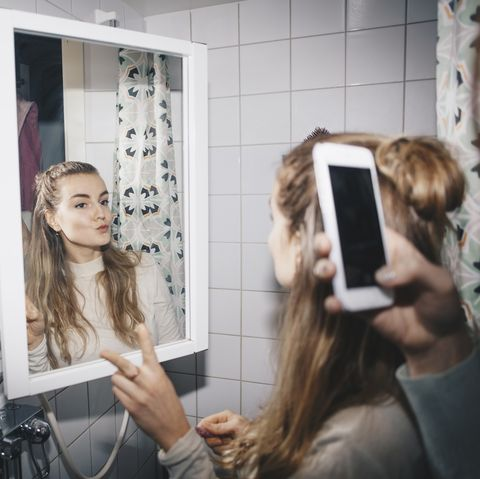 Cropped hand of woman photographing female friend in mirror reflection at dorm bathroom