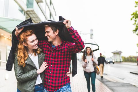 Couple walking outdoors in rain, holding jacket over their heads to keep dry