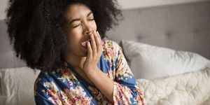 African American woman sitting in bed and yawning