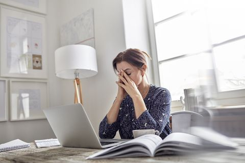 Tired, stressed businesswoman at laptop with head in hands