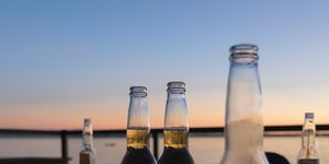 Beer Bottles By Sea Against Sky During Sunset