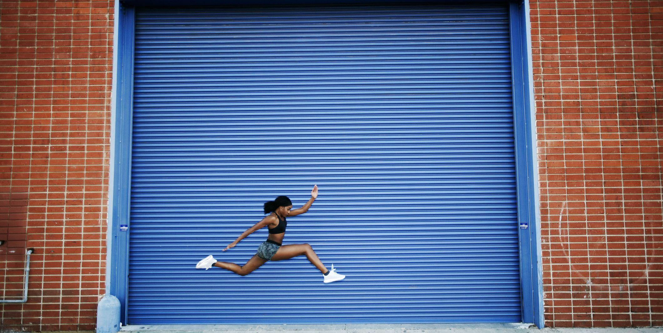 Mixed Race woman running and jumping near blue garage door