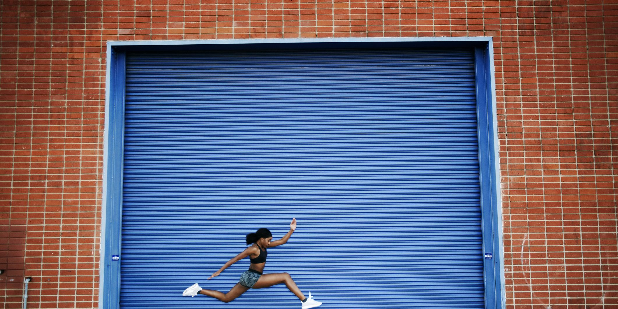 Mixed Race woman running and jumping near blue garage door