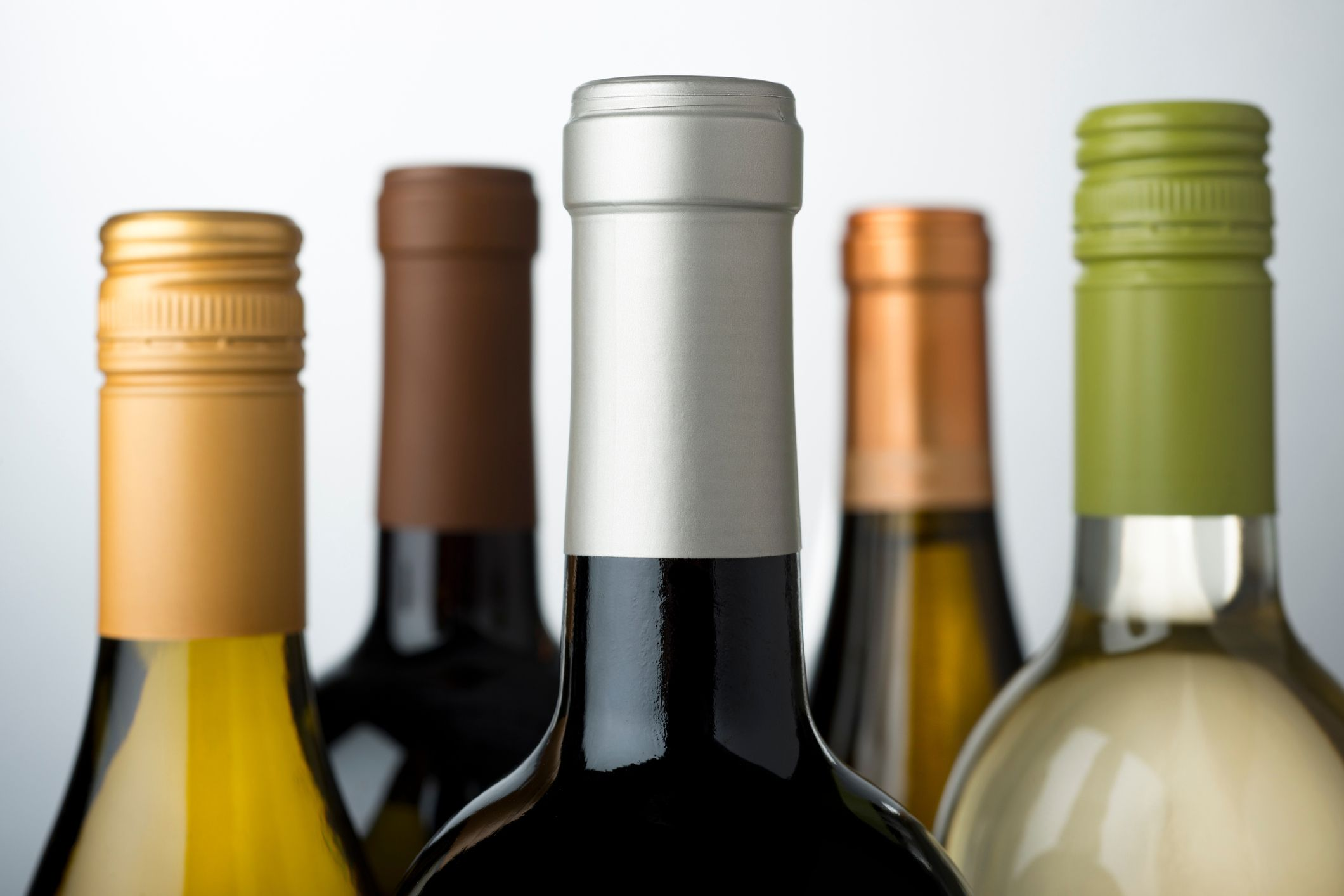 Close-Up Of Wine Bottles Against Gray Background