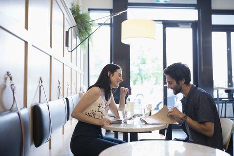 Couple looking at menus at cafe tablet