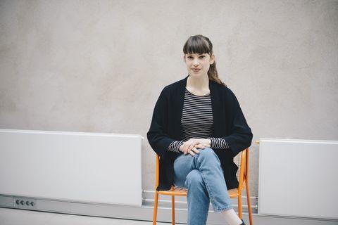 vrouw zit op een stoel met haar benen over elkaar