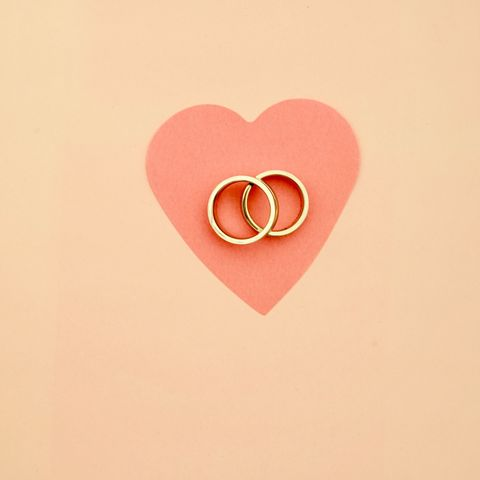High Angle View Of Wedding Rings And Heart Shape Paper On Table