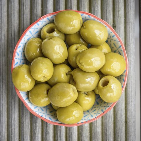 High angle close up of bowl of green olives.