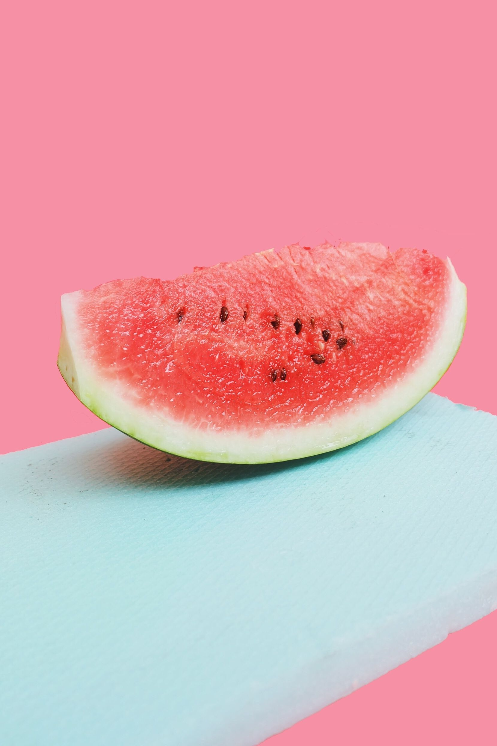 Close-Up Of Watermelon Slice On Cutting Board Against Pink Background