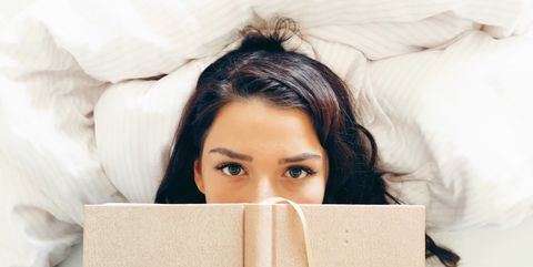 High Angle Portrait Of Woman Holding Book While Lying On Bed