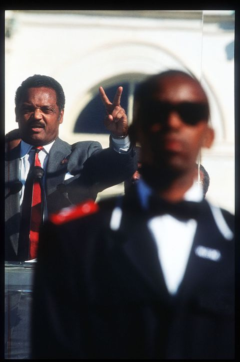 239824 05 reverend jesse jackson speaks to the crowd and gestures a victory sign while a member of the nation of islam stands guard at the million man march october 16, 1995 in washington, dc the purpose of the march was to galvanize men to respect themselves and others spiritually, morally, mentally, socially, politically and economically photo by porter giffordliaison