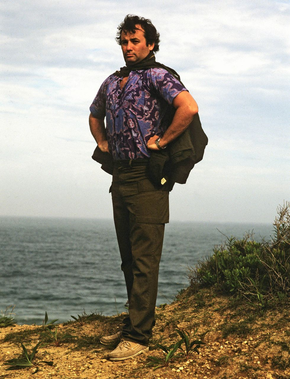 Portrait of Bill Murray as he stands, hands on his hips, on a sea-side cliff-edge during a photoshoot for Rolling Stone magazine, 1981.