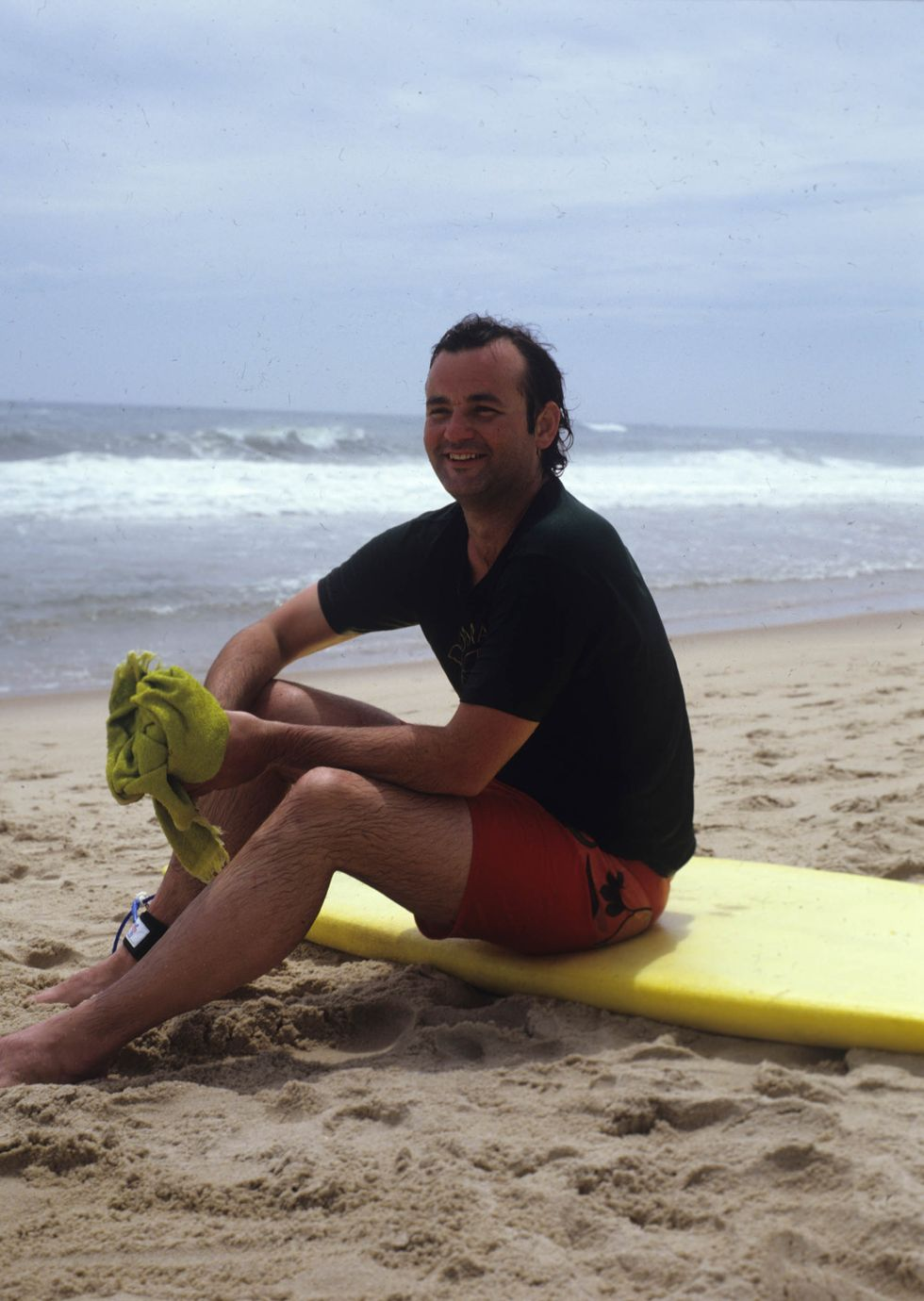 Portrait of Bill Murray, in a t-shirt and swimming trunks, as he sits on a yellow surfboard on the beach during a photoshoot for Rolling Stone magazine, 1981.