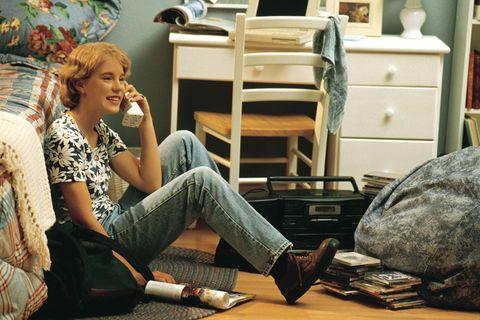 chica sentada en el suelo de su habitación con un teléfono antiguo ellees