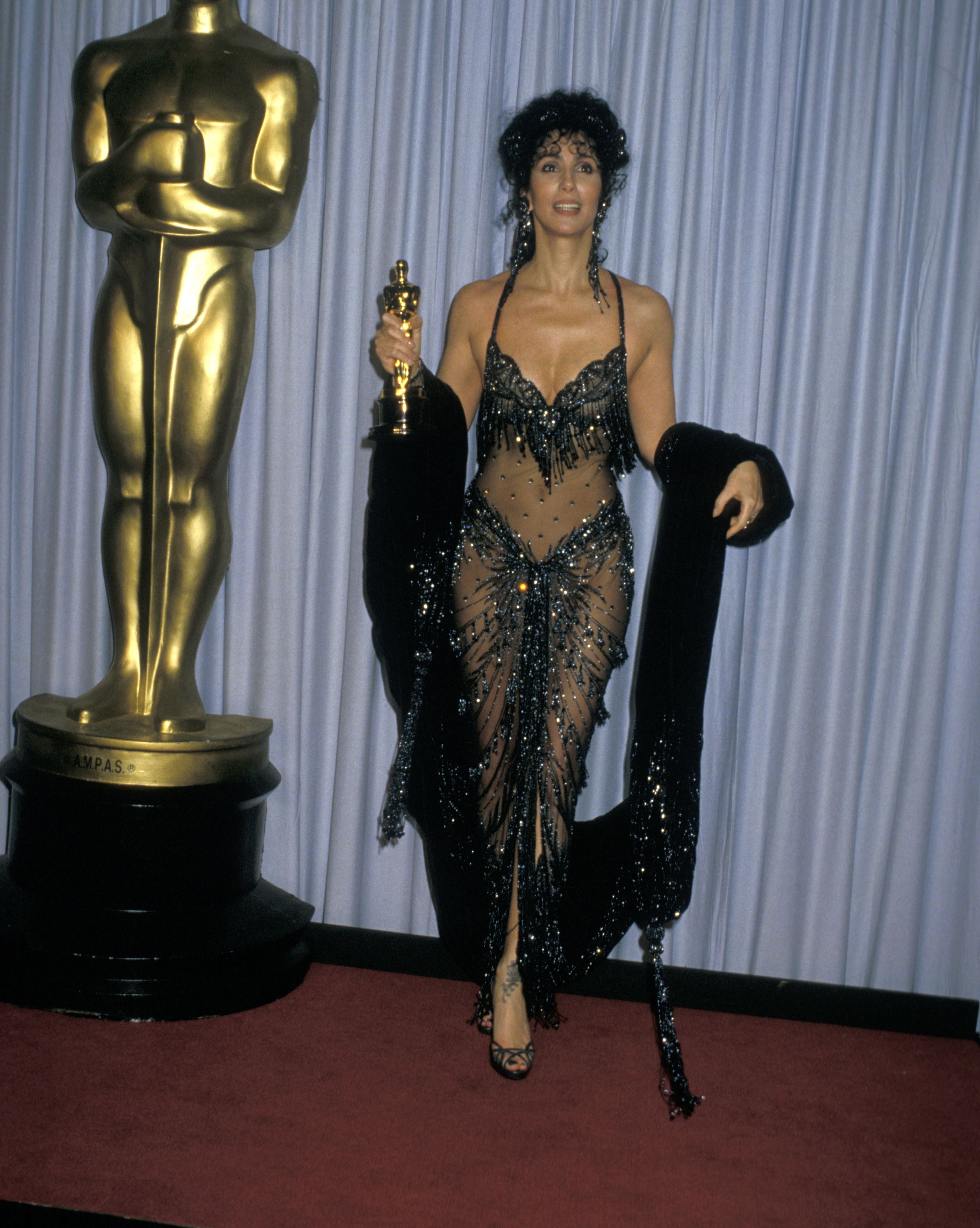 Cher holds her Oscar for best actress in the film Moonstruck .