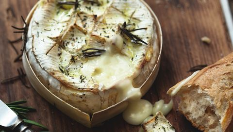 Baked camembert in oven with herbs on a wooden table.