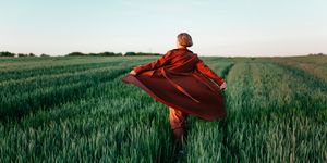Woman in red coat  walking  in the field at sunset