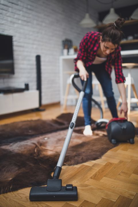 Young woman using vacuum cleaner to clean