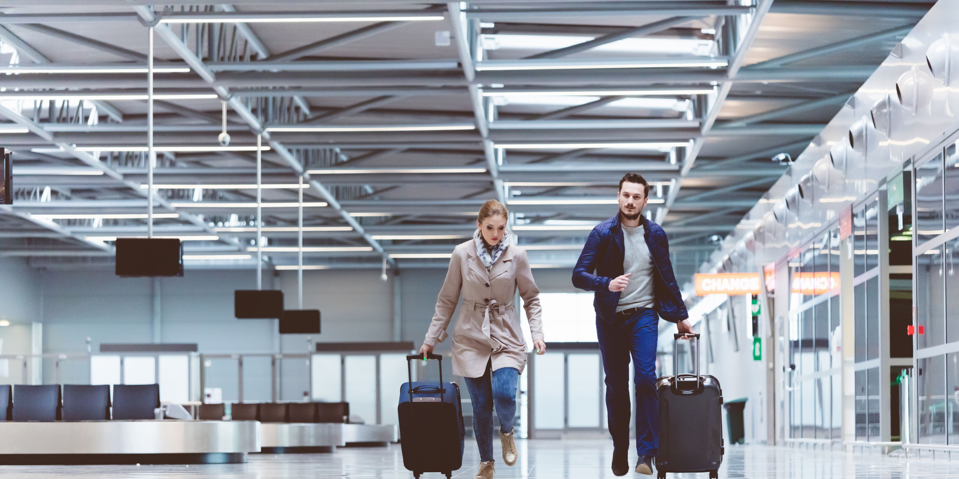 Young couple running towards boarding gate in airport