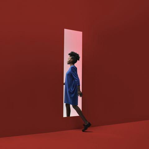 Woman walking threw rectangular opening in coloured wall