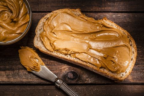 Peanut butter on bread slice shot on rustic wooden table