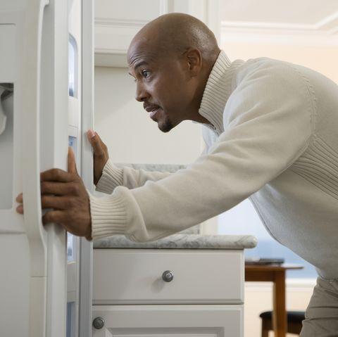 man looking in fridge for food cravings