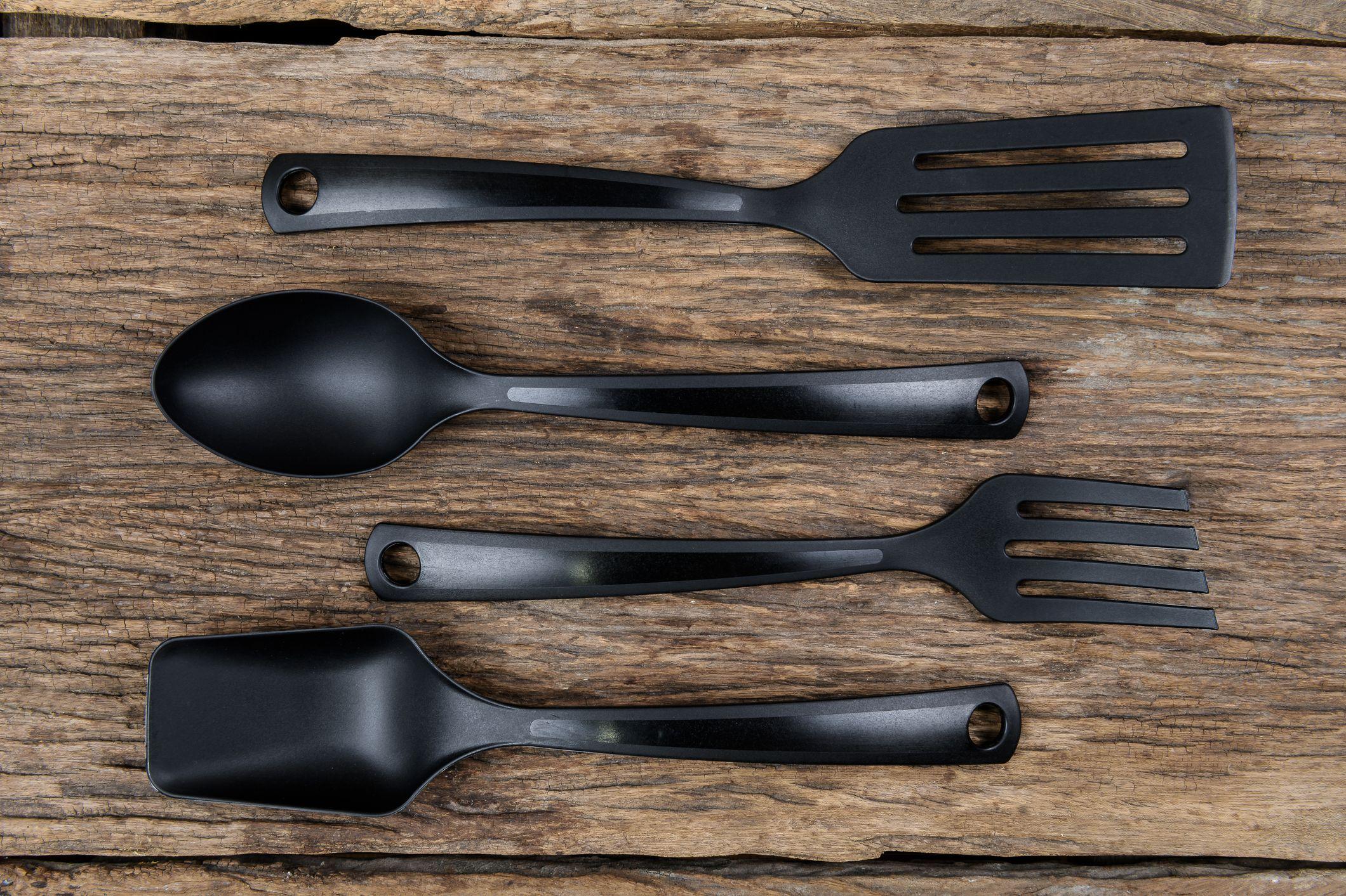 black plastic kitchen set skimmer, spade of frying pan on wooden