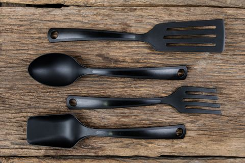 black plastic kitchen set skimmer, spade of frying pan on wooden