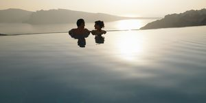 Couple in swimming pool, sunset
