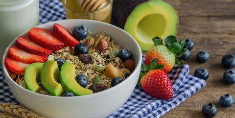 muesli or granola on white bowl with fresh fruits nuts and cereal granola top with blueberries strawberries and avocado served with milk and honey for breakfastgranola is healthy food for dieting