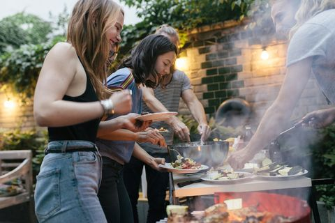 a young group of friends are helping themselves to freshly prepared food at a summer evening barbecue