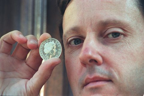 medallist and sculptor ian rank broadley, in london today weds, holding a coin bearing  the new portrait of the queen, wearing the tiara which was given as a wedding present from her grandmother queen mary, fifty years ago next month  the newly minted coins will be available  from january 1, buckingham palace announced today  eds please note this coin is only a model and has no monetary value see pa story royal coins photo by tony harris   photo by pa images via getty images