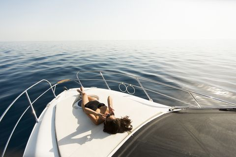 view at young attractive woman poses on  luxury yacht floating on sea