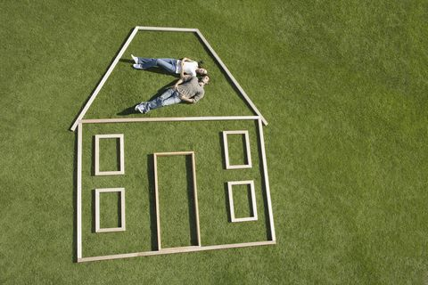couple lying on grass inside wooden house outline