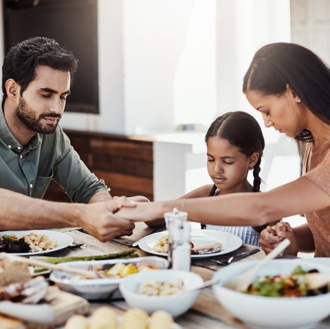 shot of a young family holding hands in prayer before having a meal together outdoors