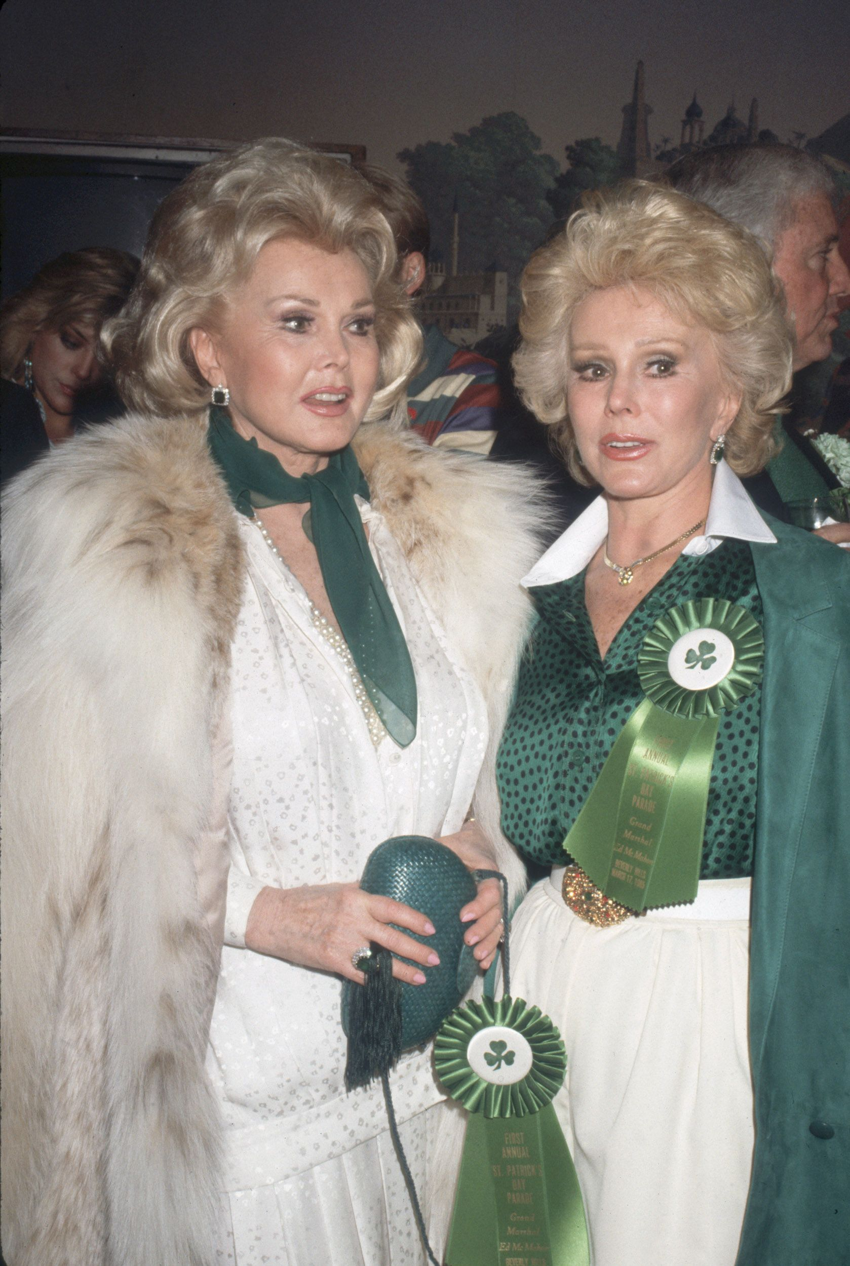 Hungarian-born sisters Zsa Zsa Gabor and Eva Gabor pose together at Jimmy's Restaurant, both sporting green ribbons from the First Annual St. Patrick's Day parade, Beverly Hills, California, March 17, 1985.