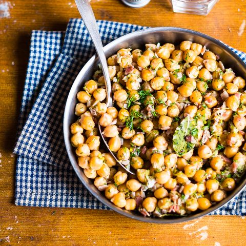 Roasted chickpea with bacon and bay leaves in a pan on a wooden table, selective focus
