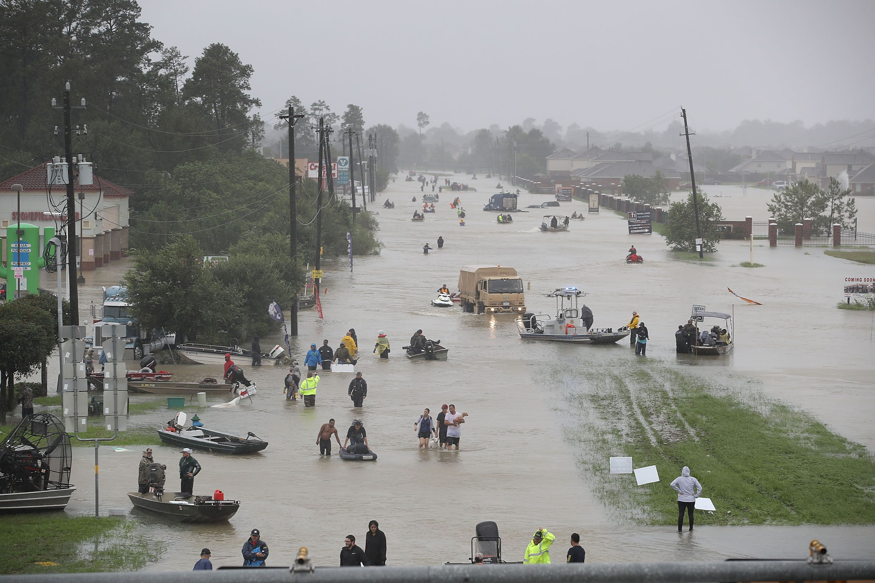 People walk down a flooded street as they evacuate their homes after the area was inundated with flooding from Hurricane Harvey on August 28, 2017 in Houston, Texas.