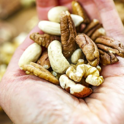 Woman holding handful of fresh nuts. Mixed whole nuts. Nut Sources of Vitamin B9 Folate