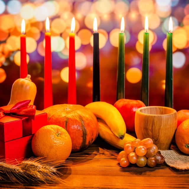 kwanzaa holiday concept with decorate seven candles red, black and green, gift box, pumpkin, bowl and fruit on light blur bokeh background
