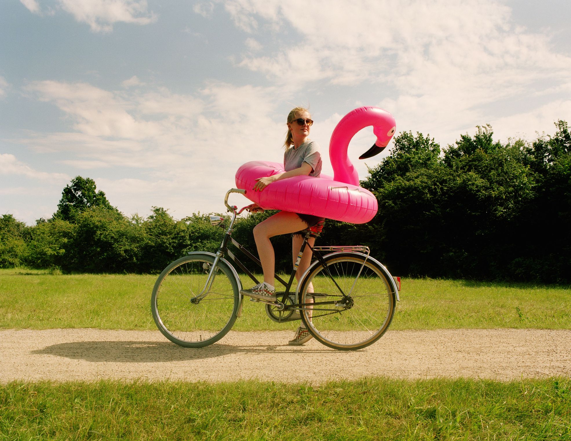 woman riding bike with flamingo float