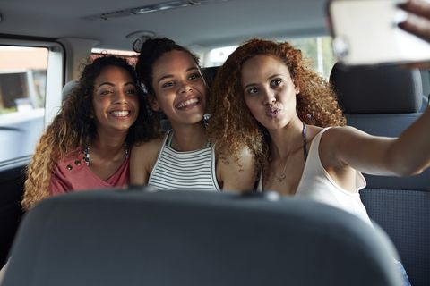 Young women smiling and making selfie in the backseat of car