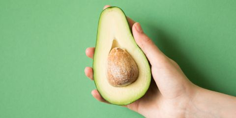 avocado in a hand of woman colored background. healthy food concept