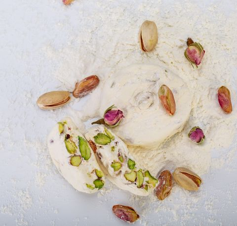 Top view Traditional Iranian and Persian pieces of white nougat dessert sweet candies (Gaz) with Pistachio nuts from Isfahan City empty space for typing text