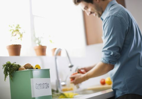 Man in kitchen with compost bin